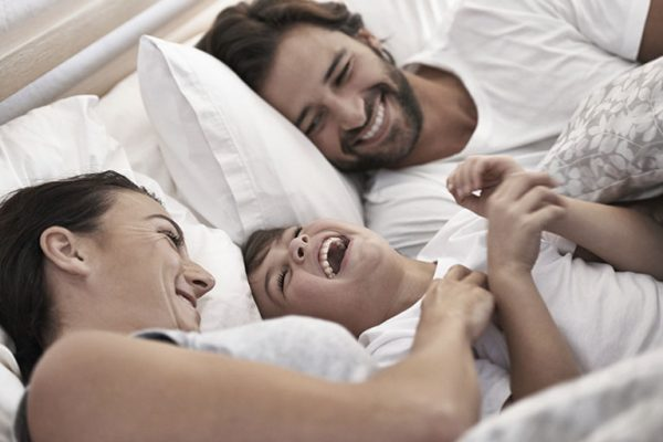 Cropped shot of a young family in bed together